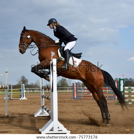 JAROSZOWKA, POLAND - APRIL 16: An unidentified competitor jumps with her horse during the international jumping competition on April 16, 2011 in Jaroszowka, Poland. - stock photo
