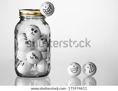 Jarred up - Conceptual Image - Trapped, Escaping, Overworked, etc. Ping Pong balls in a jar with bored faces on them, and happy ones escaping from the jar - stock photo
