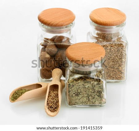 jars and wooden spoons with parsley, nutmeg and cumin isolated on white - stock photo