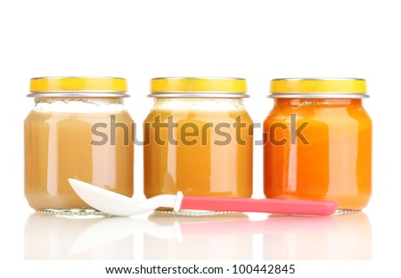 Jars of baby puree and spoon isolated on white