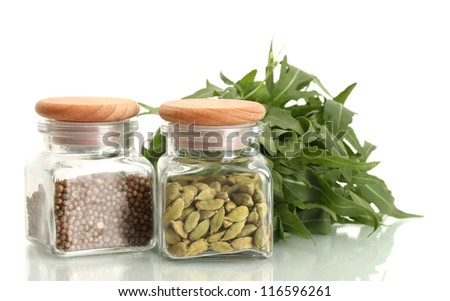 Jars of coriander seeds and green cardamom isolated on white close-up - stock photo