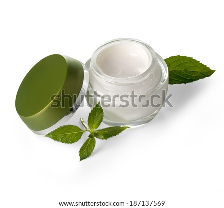 Jars of cream with green leaves isolated on white With clipping path
