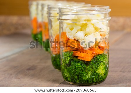 Jars of fresh cut vegetables ready to prepare for preserving - stock photo