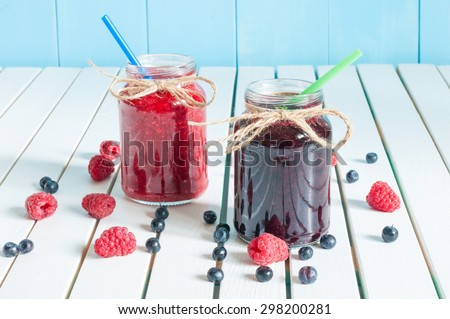 Jars of fruity jams on white background. Preserved fruits. - stock photo