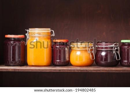 Jars of jam on a shelf - stock photo