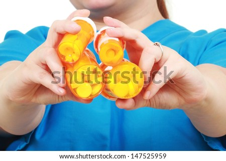 Jars of medicines in a hand of a nurse - stock photo