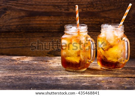 jars of peach iced tea on wooden table - stock photo