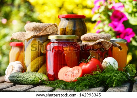 Jars of pickled vegetables in the garden. Marinated food - stock photo