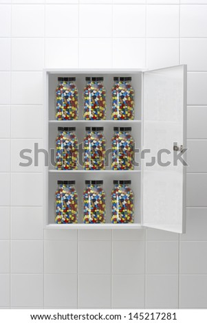 Jars of pills in bathroom cabinet - stock photo