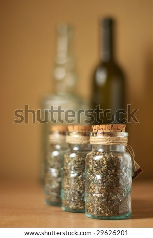 Jars of spices and vintage bottles on brown wood surface. - stock photo