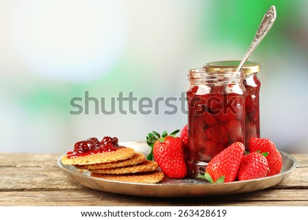 Jars of strawberry jam with berries and wafers on table on bright background - stock photo