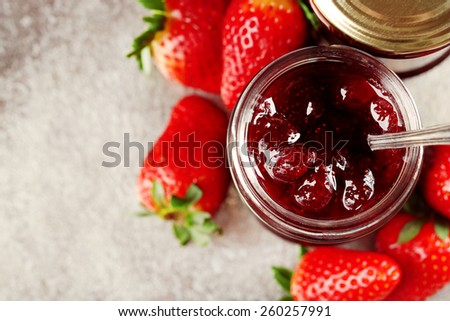 Jars of strawberry jam with berries on tray close up - stock photo
