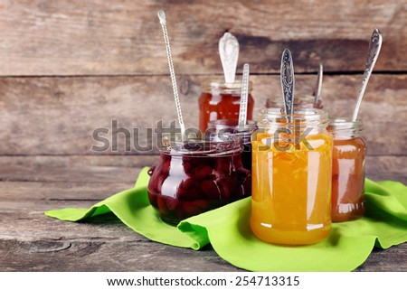 Jars of tasty jam with napkin on wooden background - stock photo