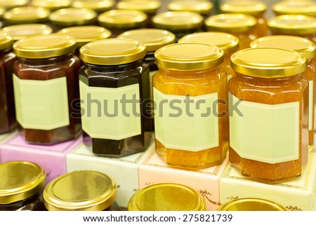 Jars of tasty several type of jam - apricot , peach , blueberry , strawberry , orange on merchandise shelf - stock photo