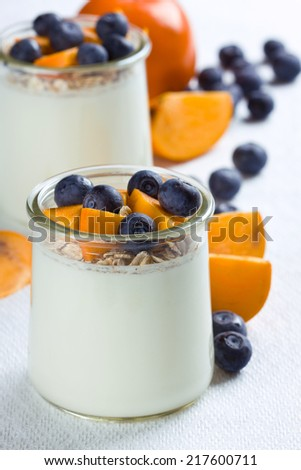 Jars of yogurt topped with blueberries and persimmon pieces - stock photo