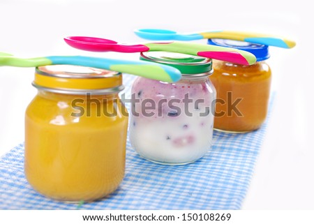 jars with baby food and spoons isolated on white - stock photo