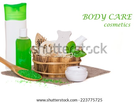 Jars with body care cosmetics, accessories in wooden basket, sea salt in wooden spoon and face cream on hessian cloth napkin isolated on white background