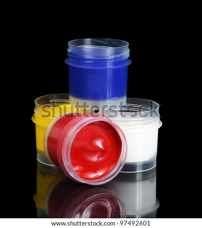Jars with colour paints on black background - stock photo