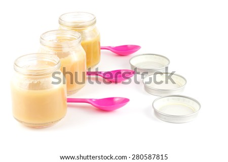 Jars with fruit puree, pink plastic spoon and a cover on a white background - stock photo