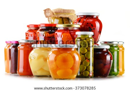 Jars with fruity compotes jams and pickled vegetables isolated on white background. Preserved fruits - stock photo