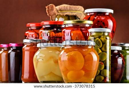 Jars with fruity compotes, jams and pickled vegetables. Preserved fruits - stock photo