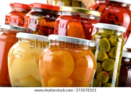 Jars with fruity compotes jams and pickled vegetables. Preserved fruits - stock photo