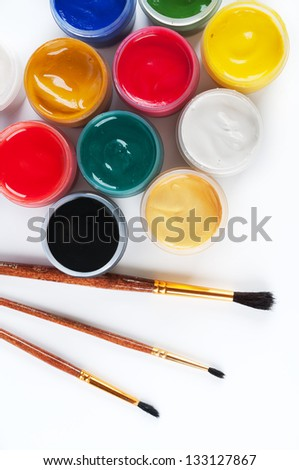 Jars with gouache and paint brushes. On a white background