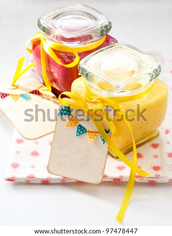 Jars with homemade fruit curd with tags on the jars - stock photo