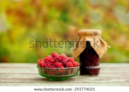 jars with jam and ripe raspberries, soft green and red nature background  - stock photo