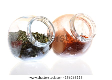 jars with pepper and lovage spices isolated white background