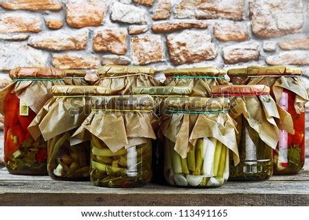Jars with pickled vegetables colorful on wooden shelf against stone wall - stock photo