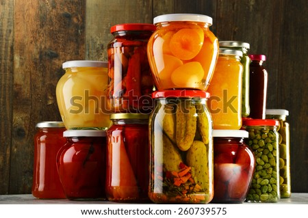 Jars with pickled vegetables, fruity compotes and jams in cellar. Preserved food