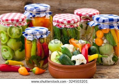 Jars with pickles, green tomatoes, cayenne pepper, mixed salad and chillies
