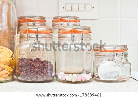 Jars with various food items in a home kitchen - stock photo