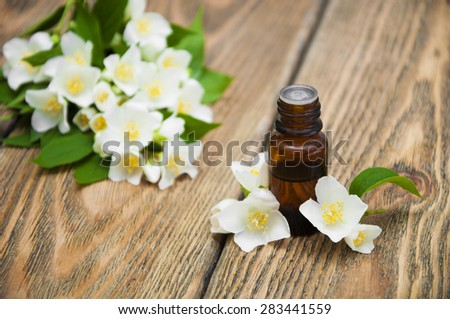 Jasmine essential oil with jasmine flowers on a wooden background