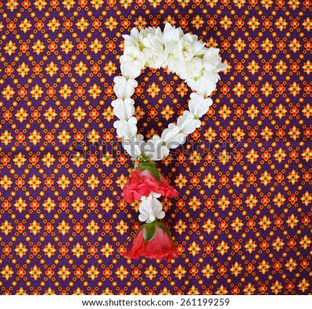 Jasmine garland with red rose on Thai fabric, Thai flower name Malai. - stock photo