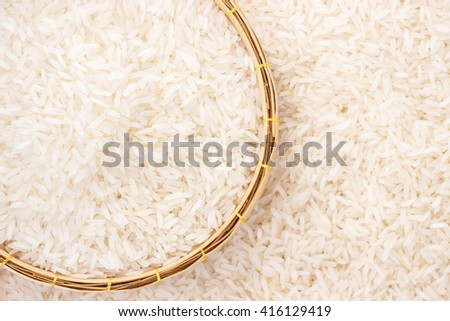 Jasmine rice in in weave basket on rice background with copy space - stock photo