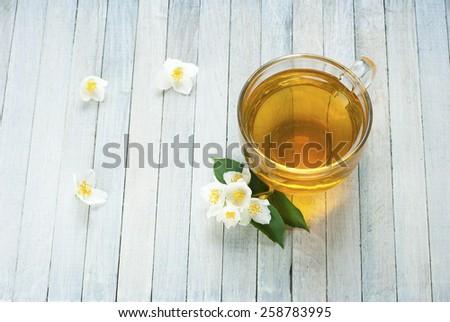 jasmine tea and jasmine flowers on white wooden background, top view - stock photo