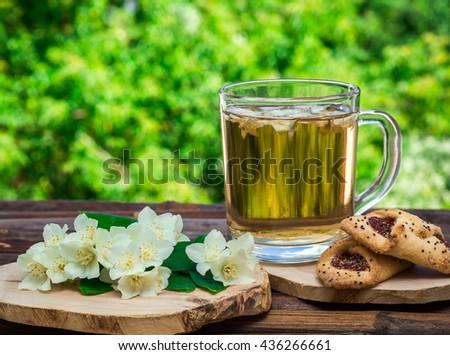 Jasmine tea cookies and jasmine flowers on vintage wooden table - stock photo