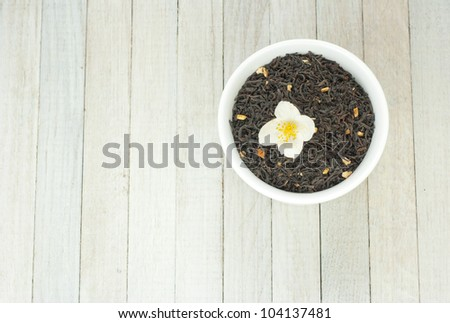 jasmine tea crops in china dish  with jasmine flowers on wooden background - stock photo