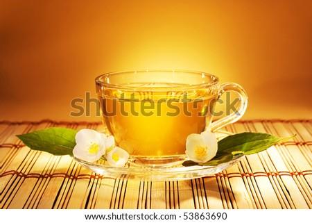 jasmine tea in soft warm evening light with fresh jasmine leaves and flowers - stock photo