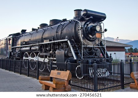 JASPER, CANADA - APR 15, 2015: Close up view of the CN 4-8-4 steam locomotive on display at the Jasper train station across the street from downtown Jasper. - stock photo