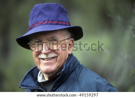 Jaunty dapper active senior man with hat, glasses, mustache, handsome, smiling. - stock photo