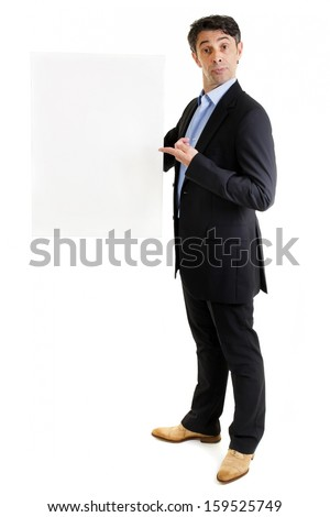 Jaunty salesman or business professional in a stylish suit standing pointing to a blank sign that he is holding in his hand with a comic expression, isolated on white