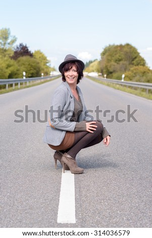 Jaunty trendy young woman crouching on the centre white line on a rural road in her stilettos and hat smiling happily at the camera - stock photo