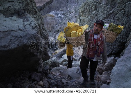 Java, Indonesia - April 4, 2016: The workers were carrying sulfur ore in Kawah Ijen Vacano. The Ijen volcano complex is a group of stratovolcanoes in the Banyuwangi Regency of East Java, Indonesia.