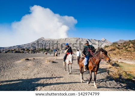 JAVA,INDONESIA-AUGUST 11:Indonesia man with the horse for tourist rent at Mount Bromo on August 11,2009 in Java , Indonesia.Mt. Bromo is an active volcano and part of the Tengger massif, in East Java. - stock photo
