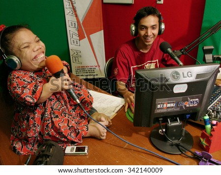 JAVA, INDONESIA - December 2, 2008: An unidentified female dwarf is interviewed by a radio presenter about Indonesian disability rights at a radio station on December 2, 2008 in East Java, Indonesia. - stock photo