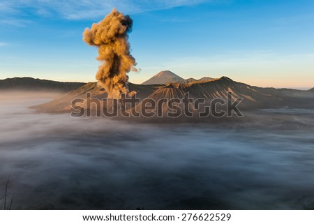 JAVA, INDONESIA - JULY 2, 2011: Mount Bromo erupts spewing out ash and smoke in the misty morning. Indonesia sits on the 'ring of fire' with many active volcanoes and prone to earthquakes. - stock photo