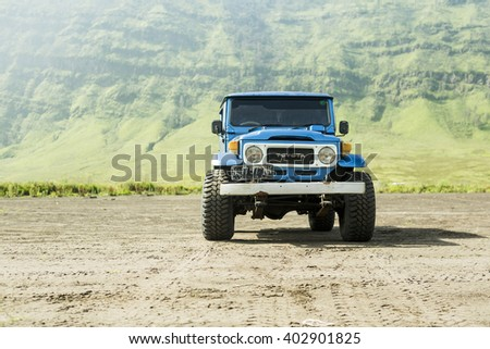 Java, Indonesia- March, 24, 2016 : Blue 4x4 Jeep for tourist at caldera of volcano Mount Bromo, East Java , Indonesia. - stock photo